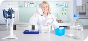 scientific expert for recombinant proteins plus polyclonal antibody in the lab - pipetting SDS-PAGE, glas flask and several pipette rack in the front